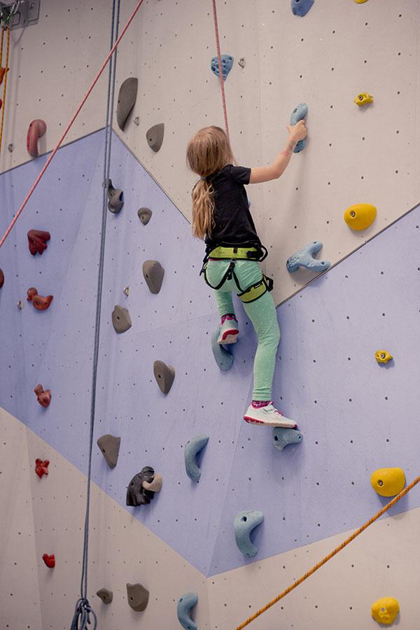 Das große Kind sucht sich seinen Weg an der Kletterwand (Toprope), während papa unten für die Sicherung sorgt.