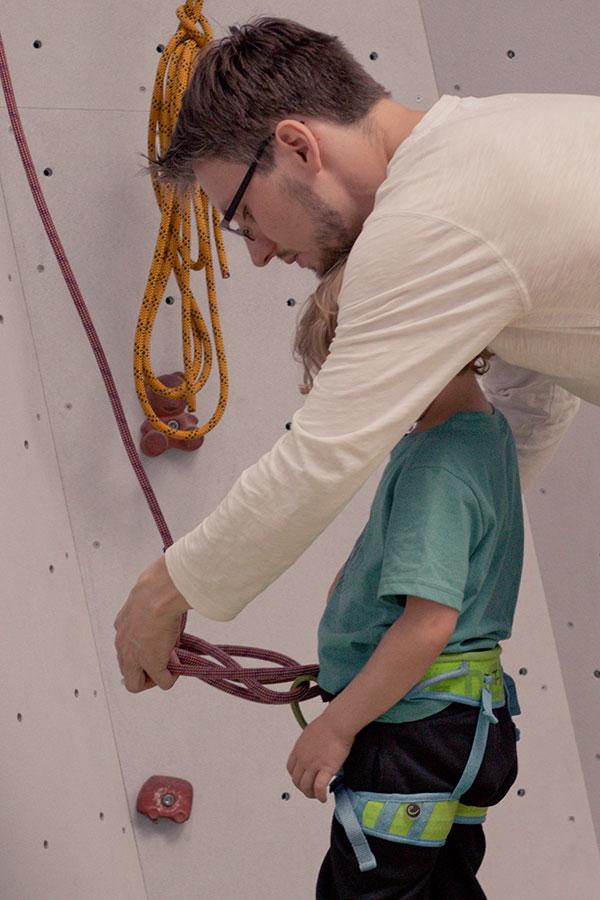 Papa sichert das Kind in der Kletterhalle mit einem Achterknoten.