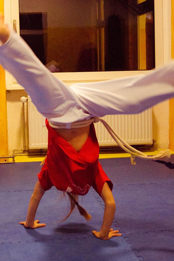 Kind übt Radschlag beim Capoeira Training