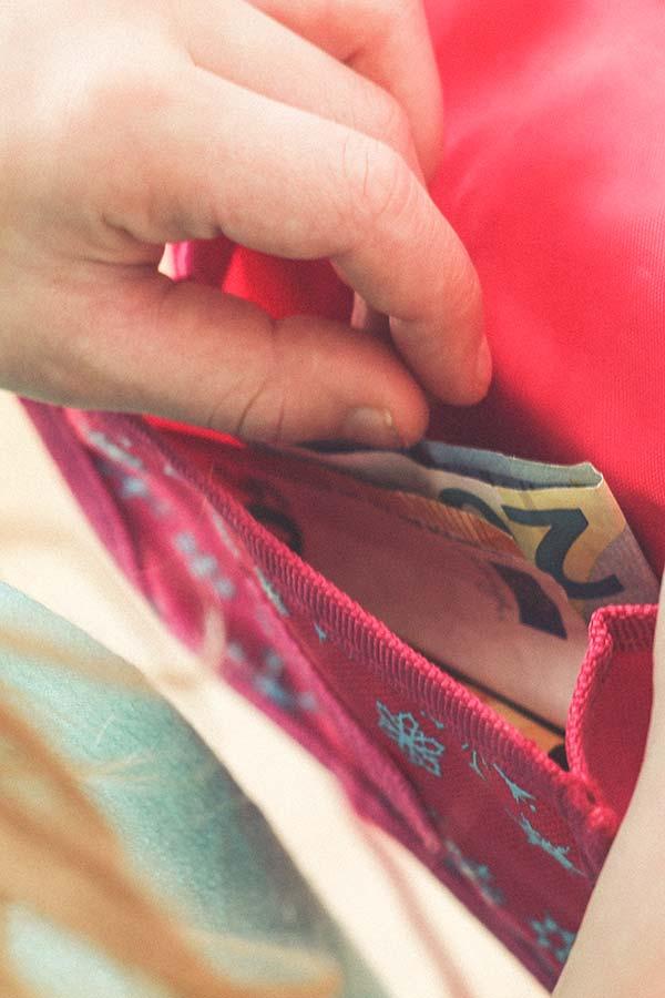 Kind nimmt Geld aus Portemonnaie