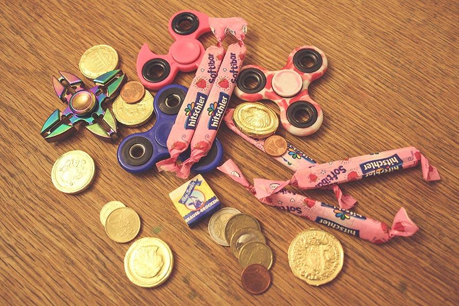 Das Kind kauft Süßigkeiten und Fidget Spinner