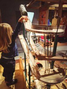 Ein Kind probiert die Murmelbahn der Tüftelmäuse